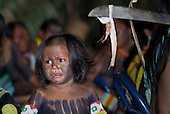 "Altamira, Brazil. ""Xingu Vivo Para Sempre"" protest meeting about the proposed Belo Monte hydroeletric dam and other dams on the Xingu river and its tributaries. Kayapo child and a machete with a piece of the representative from the electricity company shirt tied to it."