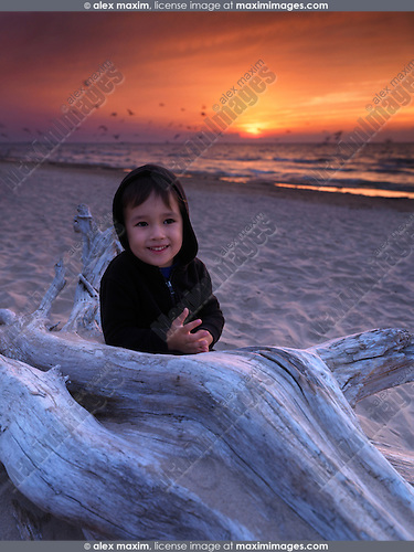 Portrait of a cute three year old boy standing at the beach with beautiful red sunset in the sky. Lake Huron, Ontario, Canada.