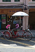 Traditional rickshaws parked on the street at the UNESCO heritage town - Georgetown of Penang, Malaysia. Photo: Sanjit Das/Panos
