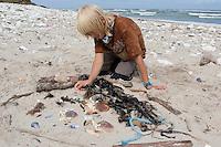 Kind legt aus allerlei Fundstücken ein Bild auf den Sandstrand, Krebspanzer, Muschelschalen, Tang, Steine, Stöckchen, Naturkunst am Strand, Strandkunst, Meer, Küste,