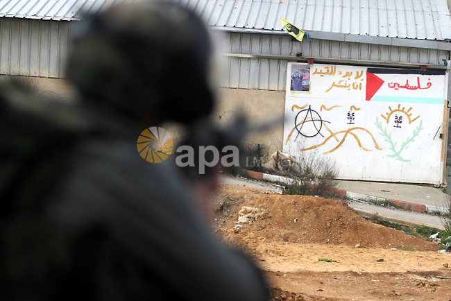 An Israeli security officer rubbers towards Palestinian protesters during clashes next to the Israeli military prison 'Ofer' in Beitunya, south of the West Bank city of Ramallah, on February 24, 2013 following the death of a Palestinian prisoner held in Israel. Some 3,000 Palestinians held in Israeli jails were staging a one-day hunger strike in protest at the death of the inmate Arafat Jaradat, an official said, as security forces clashed with demonstrators in the West Bank. Photo by Issam Rimawi