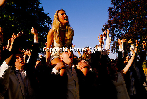 MALE CARRYING FEMALE ON HIS SHOULDERS, WITH CROWD OF REVELLERS, AT THE ROYAL AGRICULTURAL COLLEGE BALL, CIRENCESTER, GLOUCESTERSHIRE,