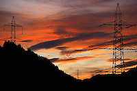 Silhouette of a high tension pole with forest, mountains and a mystical sunset sky in the background