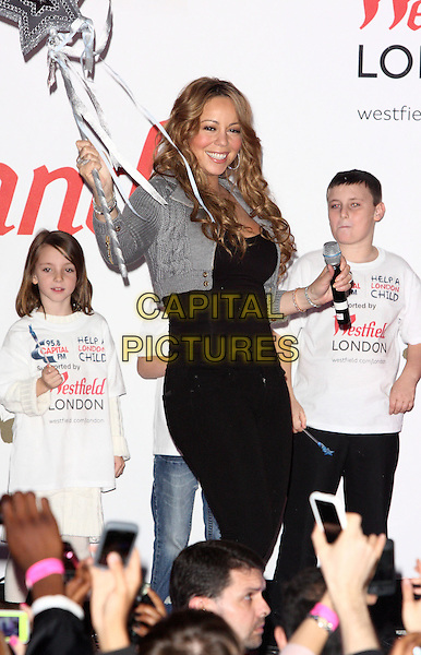 MARIAH CAREY.turns on the Christmas Lights at Westfield Shopping Centre, London, England, UK, November 19th 2009..half length microphone black grey gray cropped jacket knitted top jeans trousers silver bracelets  smiling  wand star holding .CAP/ROS.©Steve Ross/Capital Pictures.