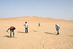 """Shooting of the series """"Wahet Al Gheroub"""" (""""Sunset Oasis"""") Egypt, April 2017 (El Adl Group). Members of the crew are sweeping the sand to the make the desert look untouched before shooting the scene.<br /> <br /> Tournage de la série """"Wahet Al Gheroub"""" (""""Le crépuscule de l'Oasis"""") Egypte, Avril 2017 (El Adl group). Des techniciens préparent la scène, et balayent le sable pour que le désert paraisse vierge de passage"""