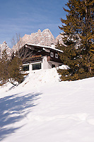 The imposing peaks of the Dolomites rise behind a chalet surrounded by snow