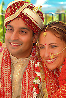 Tradditional Hindi wedding with groom wearing carnation flowers and bride with indian adornments
