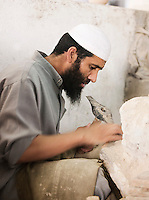 An artisan sculptor in a workshop in Fes, Morocco