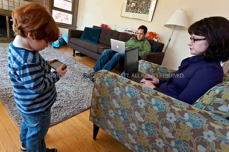 "4/23/2011--Seattle, WA, USA..Brad Kahn, 40, his wife Erin Kahn, 38 and their son Ezra, 2, in their home in Seattle, WA, checking email on their laptops while Ezra plays games on an an old iPhone 3 that Mr. Kahn no longer uses. Mr. Kahn, an environmental consultant in Seattle, said he often communicates with wife, Erin, by e-mail, even when the two are sitting a few feet apart on the sofa, tapping away on their laptops. He will cut her off if she starts instructing him verbally about what he calls his 'honey-do' list of chores for the weekend, he said, and ask her to send it electronically. It's simply more efficient, Mr. Kahn, 40, explained: ""If I misunderstood any directions, having a written record can be very useful in maintaining marital bliss."" ..©2001 Stuart Isett. All rights reserved."