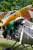 The green Kinner Radial Engine and wooden propeller on this silver Meyers OTW (out-to-win) bi-plane with red and white wings standout against the green grass and trees at the Galway Wings 'n' Wheels 2010 Showcase. Three of the engine's five cylinders are prominent as is a chrome exhaust.