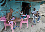 A family sits in front of their home in Batey Bombita, a community in the southwest of the Dominican Republic whose population is composed of Haitian immigrants and their descendents.