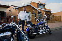 SOWETO, SOUTH AFRICA MARCH: Afrika Tau, age 31, waits to pick up a friend with his Harley Davidson motorcycle in Soweto, South Africa. He grew up in Soweto and he is now a successful executive working for Cisco and lives in a house in Kyalami, a wealthy suburb north of Johannesburg. He drives a new BMW and relaxes with his motorbike on the weekends. Afrika is one of the recent educated and affluent black people that has grown up in the poor townships but now are living a middle-class or affluent life in the former white suburbs. (Photo by: Per-Anders Pettersson)