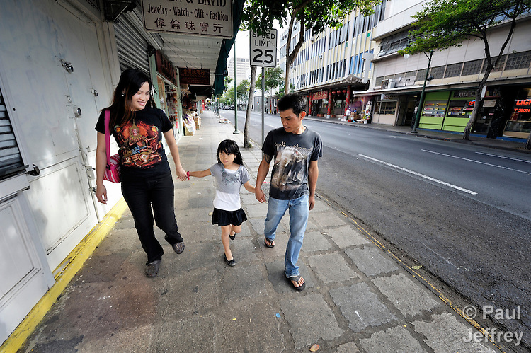 Singha Naubon, a Thai survivor of human trafficking, walks with his wife Thamonwan and their 7-year old daughter Thanisorn through the streets of Honolulu, Hawaii. They have received assistance and support from the Susannah Wesley Community Center in Honolulu, which has played a key role in identifying and supporting victims of human trafficking.