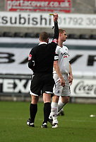 Pictured: Alan Tate of Swansea (R) sees a yellow card by referee K K Wright (L).<br />
