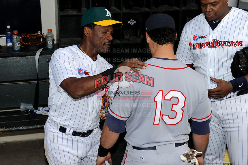Hall of Fame outfielder Rickey Henderson #24 signs the jersey of former minor leaguer David Convertini #13 after the MLB Pepsi Max Field of Dreams game on May 18, 2013 at Frontier Field in Rochester, New York.  (Mike Janes/Four Seam Images)