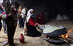 A Palestinian woman bakes bread on firewood during a rainy and cool day in Gaza city, on Dec. 05, 2013. Photo by Ashraf Amra
