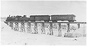 K-28 #475 with the Chili Line passenger train composed of an RPO and a coach crossing a trestle near Santa Fe.<br /> D&amp;RGW  Santa Fe Branch, NM  Taken by Jackson, Richard B.