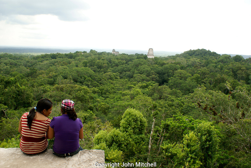 Two young women enjoying the view from the top of Temple IV, Maya ruins of Tikal, El Peten, Guatemala. Tikal is a UNESCO World Heritage Site...