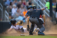 Home plate umpire David Martinez looks on as Asheville Tourists catcher Hamlet Marte (14) tags out Landon Lassiter (2) of the Kannapolis Intimidators at Intimidators Stadium on May 28, 2016 in Kannapolis, North Carolina.  The Intimidators defeated the Tourists 5-4 in 10 innings.  (Brian Westerholt/Four Seam Images)
