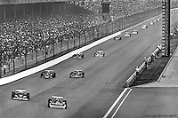 INDIANAPOLIS, IN: Gordon Johncock leads Tom Sneva, Bobby Unser, AJ Foyt and the rest of the field into Turn 1 during the Indianapolis 500 on May 29, 1977, at the Indianapolis Motor Speedway