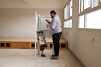 A man votes with his child in a polling station in Moqattam district in Cairo, during the first round of the presidential election. Egypt, May 23rd, 2012.