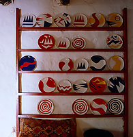 A collection of contemporary plates with graphic designs displayed on a custom made rack