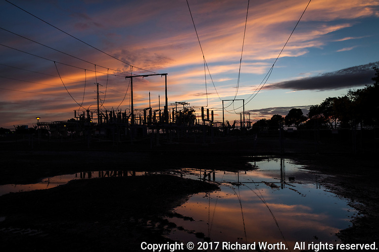 The sun sets and paints the sky while pools of rain water reflect the show at a power substation.