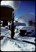 South-facing view of the Chama water tank with an approaching rotary throwing snow.<br /> C&amp;TS  Chama, NM  prior to 2/1978