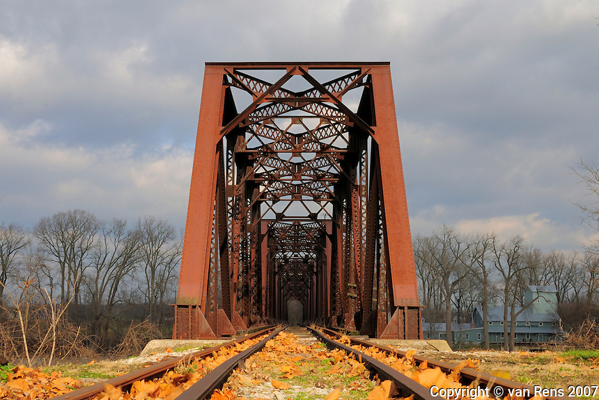 This classic steel railroad bridge is of riveted truss construction.  The bridge truss with  deck plate girders provide an approach to the structure, which sits on concrete piers. There is lattice present on the bracing and cowling.