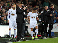Swansea manager Garry Monk shouts instructions to his players while Gylfi Sigurdsson of Swansea and Jefferson Montero of Swansea prepare to substitute team mates during the Barclays Premier League match between Swansea City and Bournemouth at the Liberty Stadium, Swansea on November 21 2015