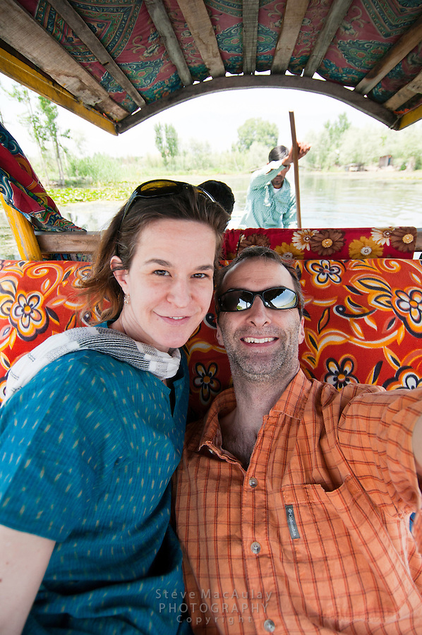 Point of view self portrait of smiling western tourists in traditional shikara, Srinagar, Kashmir, India.