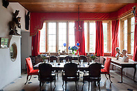The dining area off The Big Hall has a stone flagged floor and deep orange velvet curtains