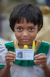 A Rohingya girl, having just crossed the border from Myanmar, shows her new identity card that she was given by United Nations workers in the Kutupalong Refugee Camp near Cox's Bazar, Bangladesh. <br /> <br /> More than 600,000 Rohingya have fled government-sanctioned violence in Myanmar for safety in Bangladesh.<br /> <br /> Parental consent obtained.
