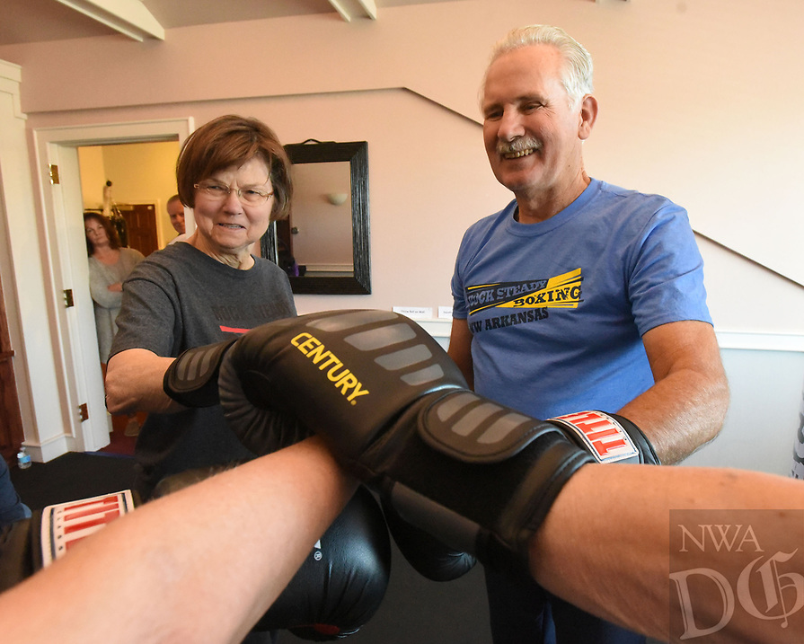 NWA Democrat-Gazette/FLIP PUTTHOFF <br /> Boxers join gloves at the end of every workout in Rogers    Dec. 5 2018 as an exercise in camaraderie. Judy Wamsher and John Brown lock gloves with teammates.