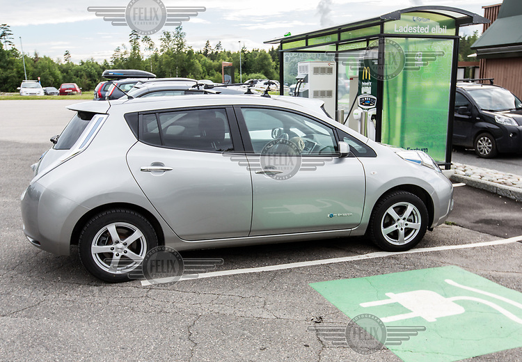 Electric car parked to be charged outside a fast food restaurant.