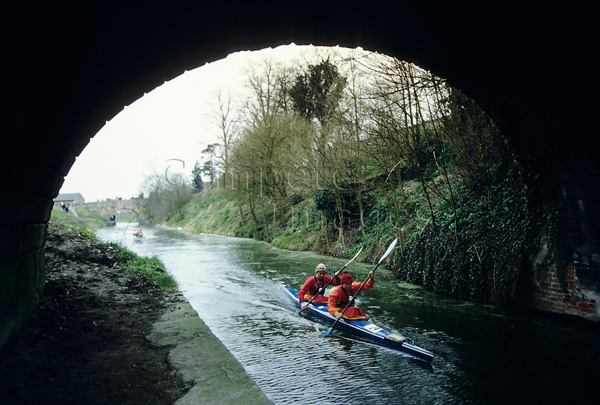 Two men Kayaking under a bridge over a river