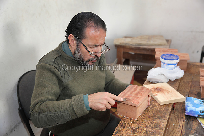 An artisan working in a workshop in decorative woodwork at the Artisan School or Dar Sanaa, founded 1919 under the Spanish Protectorate of Morocco, which teaches the traditional art and craft skills of woodwork, zellige, sculpted plaster, leatherwork, etc, in Tetouan on the slopes of Jbel Dersa in the Rif Mountains of Northern Morocco. Tetouan was of particular importance in the Islamic period from the 8th century, when it served as the main point of contact between Morocco and Andalusia. After the Reconquest, the town was rebuilt by Andalusian refugees who had been expelled by the Spanish. Picture by Manuel Cohen