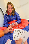 A young couple plays cards in their tent while camping in the Teton Mountain Range, Wyoming.