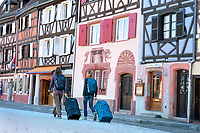 Two women with their luggage traveling in Colmar, France, exploring the colorful old city.
