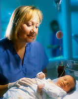 Nurse caring for newborn infant.