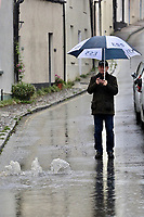 A man takes pictures of a flooded road caused by heavy rain in Crickhowell, south Wales, UK. Saturday 26 October 2019
