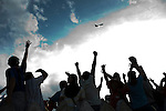 5 July 2009 - Tegucigalpa, Honduras - Supporters of ousted Honduras President Manuel Zelaya cheer as his airplane flies overhead at the international airport in Tegucigalpa. Zelaya turned back from an attempted return home on Sunday after soldiers clashed with his supporters as he tried to land, fueling tensions over the coup that toppled him. Photo credit: Benedicte Desrus