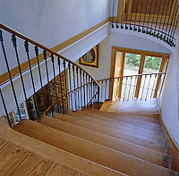 View looking down the curved wooden staircase which descends to the entrance hall