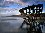 Shipwreck on a beach with reflections in the water