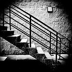High contrast stairs and railing against a brick wall.