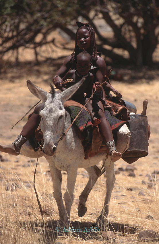 Himba mother and child on a  mule,  Northern Namibia.