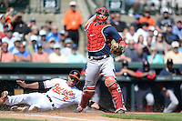 Boston Red Sox catcher Ryan Lavarnway (20) throws to first as J.J. Hardy (2) slide into home during a spring training game against the Baltimore Orioles on March 8, 2014 at Ed Smith Stadium in Sarasota, Florida.  Baltimore defeated Boston 7-3.  (Mike Janes/Four Seam Images)