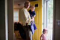 Fred Bermont, daughter Elyse Bermont (age 2.5, right) and son Dylan Bermont (age 9 months) pose for a portrait before he drops the kids off at day-care in Lexington, Massachusetts, USA, before he goes to work on June 9, 2014. Bermont is the father of two children and shares parenting duties with his wife, Jen Bermont. Fred usually takes care of the morning routine, including feeding, dressing, and dropping the kids off at day-care, and Jen picks them up and watches over them in the afternoon. Fred is a Senior Clinical Standards Specialist at Shire, a pharmaceutical company with headquarters in Lexington.