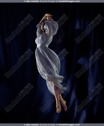 Beautiful young woman dancer in a light blue flowy dress spinning gracefully in the air in a spotlight with a black blue stage curtain in the background