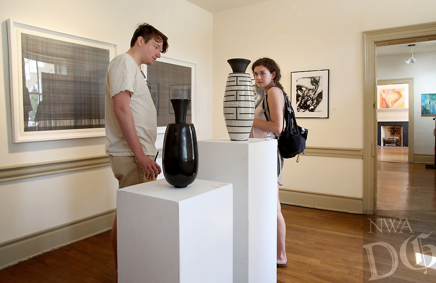NWA Democrat-Gazette/DAVID GOTTSCHALK  Luke Hankins (left) and Alaina Stout look at artwork in one of the galleries Thursday, April 13, 2017, inside the Walker-Stone House in Fayetteville. Fenix Fayetteville, a group of local artists, and Experience Fayetteville, the city's tourism bureau, are showcasing the Fenix and Friends Art Show featuring works from 26 artist. The show is open Thursday through Saturday and runs through April 29. This Saturday classes, including oil painting and monoprinting, will be open to the public.